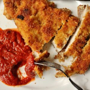 A sliced Milanese pork chop with tomato balsamic sauce on a white plate.