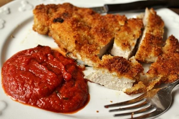 Breaded sliced pork milanese with a side of tomato sauce