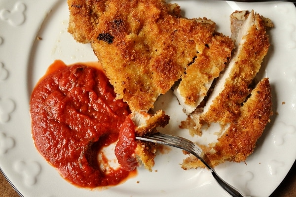 Sliced, breaded pork chop with tomato sauce on a white plate