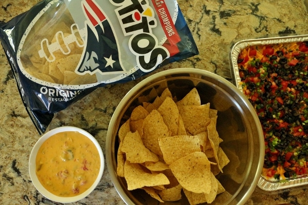 A bag of Tostitos tortilla chips, a bowl of tortilla chips, a bowl of homemade queso, and a dish of taco dip