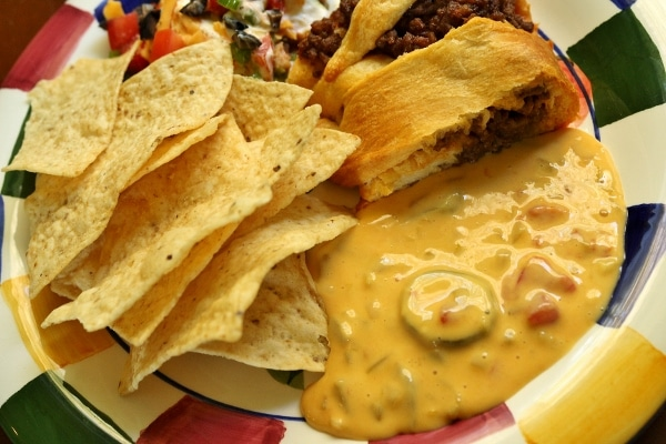 A delicious spread of taco dip, taco ring, chile con queso, and tortilla chips on a colorful plate