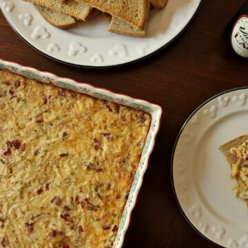 hot reuben dip baked in a colorful square dish with toasted rye bread on the side