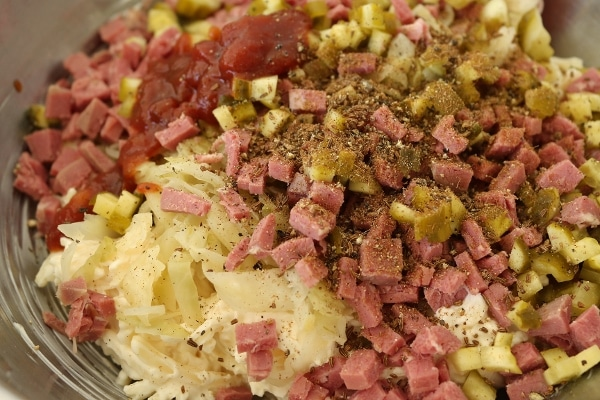Ingredients for Reuben dip in a mixing bowl, including sauerkraut, shredded cheese, chopped corned beef, pickles, ketchup, and spices.
