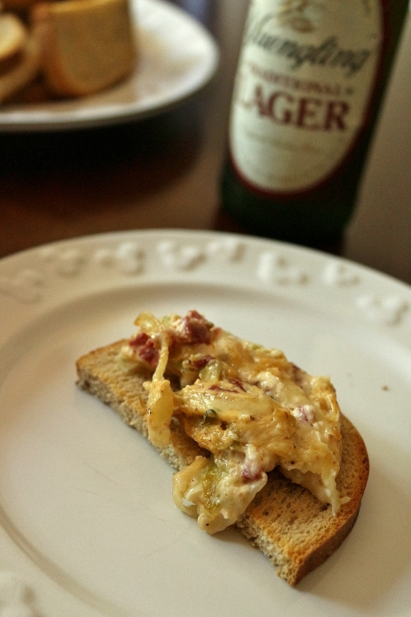 A scoop of Reuben dip served on a rye bread toast with a bottle of beer in the background