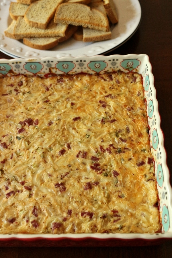 Hot Reuben dip in a square baking dish with a platter of rye toasts in the background