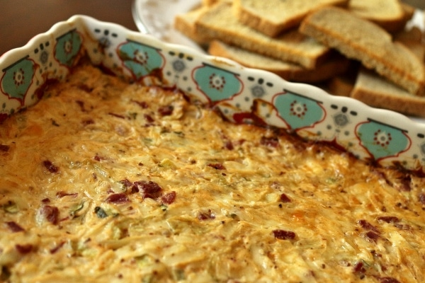 Hot Reuben dip in a square baking dish with a platter of rye bread toasts in the background