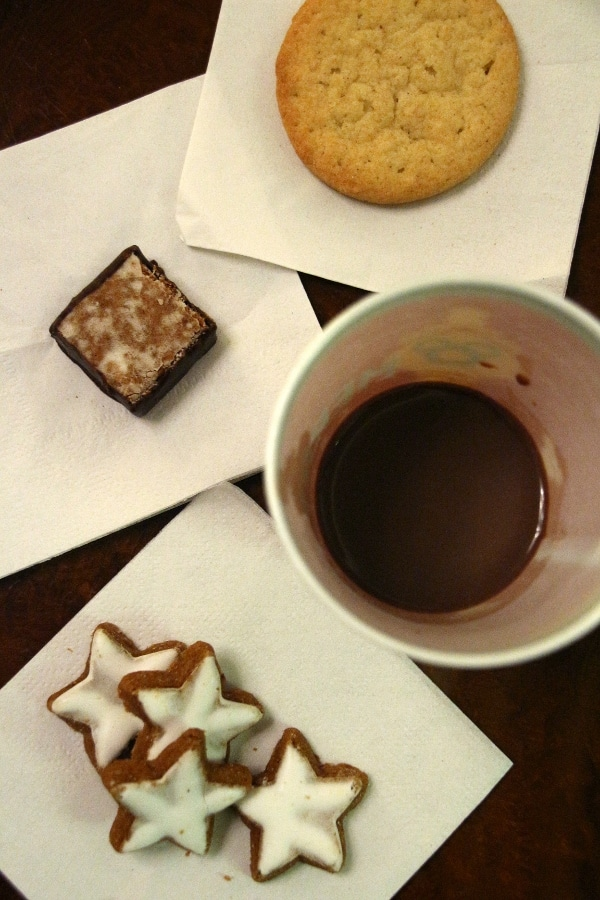 overhead view of a cup of hot chocolate and a variety of small cookies