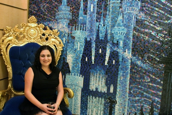 a woman sitting in front of a tile mosaic of Cinderella\'s castle