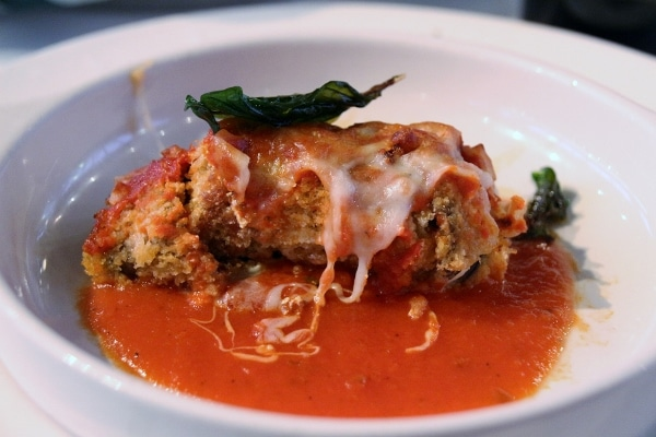 eggplant roll up with cheese on a plate with tomato sauce