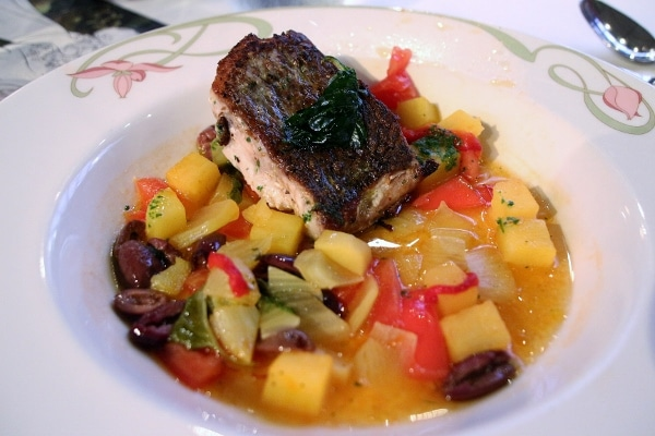 seared fish with vegetables in broth in a shallow bowl