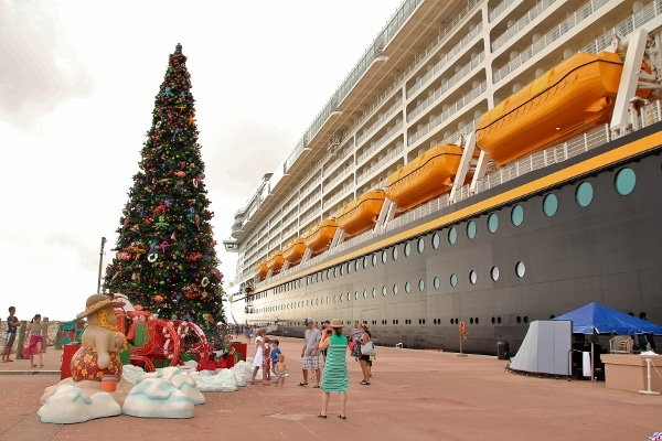 a Christmas tree next to the Disney Fantasy cruise ship