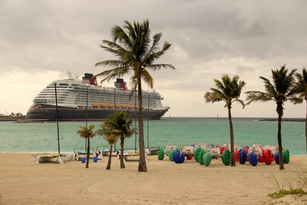 The Disney Fantasy cruise ship beyond a beach with palm trees and beach vehicles