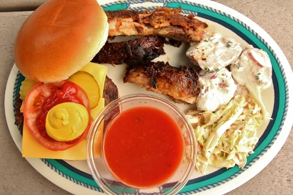 a burger, ribs, and salads on an oval plate
