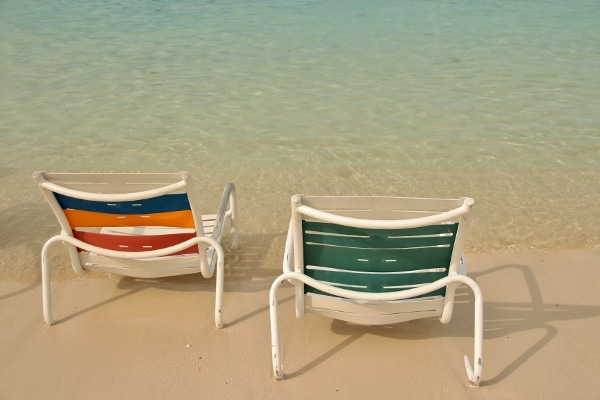 A couple of beach chairs along the shore