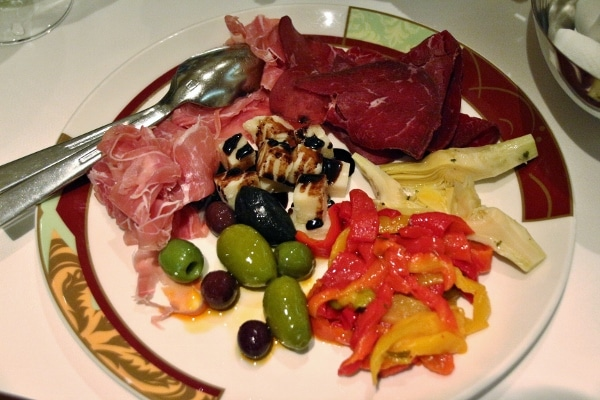 an antipasti plate with cured meats, cheese, and olives