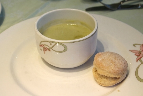 a cup of green soup with a small biscuit on the side