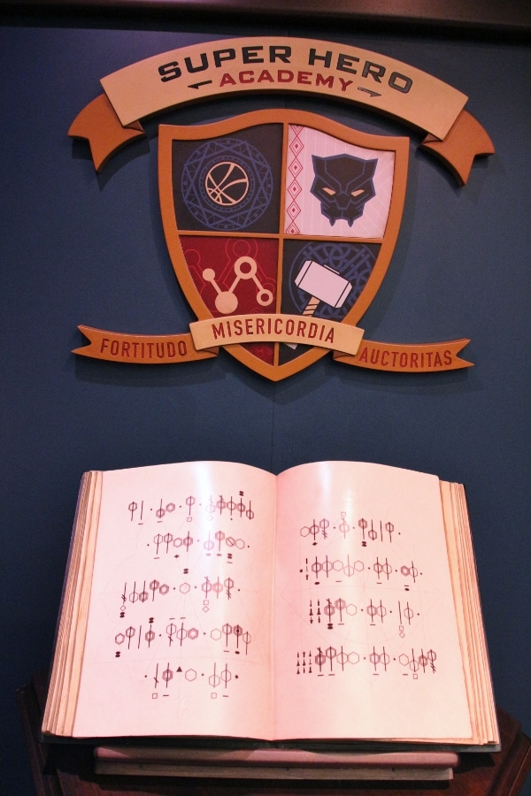 a coat of arms over an open book with codes