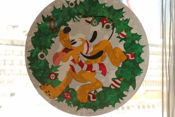 a window decoration with Pluto inside a Christmas wreath