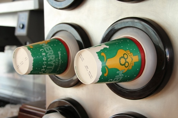 A close up of Very Merrytime Cruise themed paper cups in a dispenser
