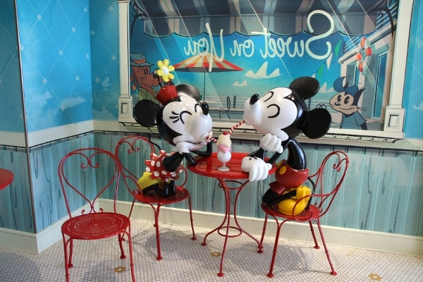 Mickey and Minnie Mouse statues sharing an ice cream