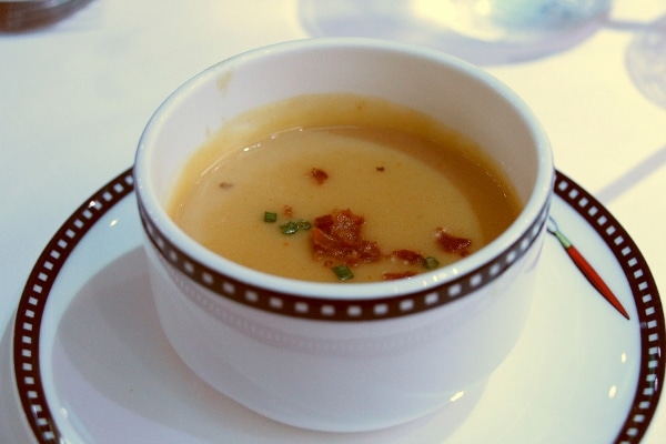 A bowl of soup garnished with bacon