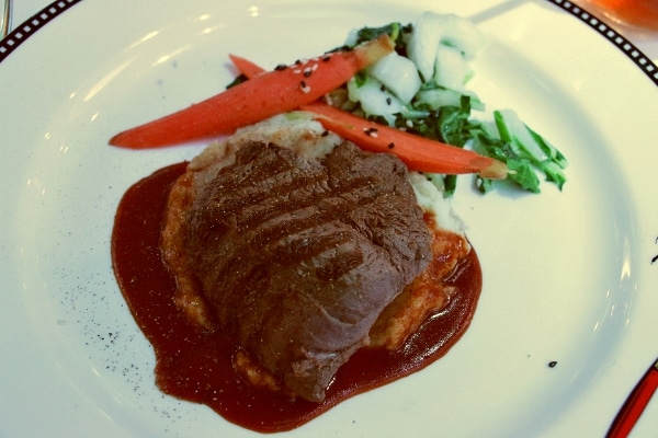 sliced steak served on a plate with vegetables and a dark brown sauce