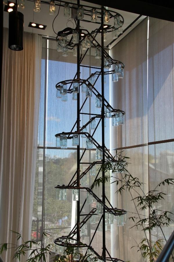 a tall display of glass bottles near a window