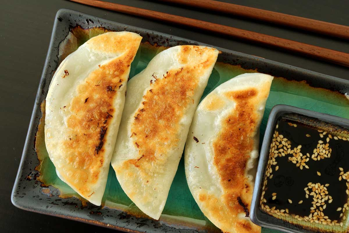 Three pan-fried dumplings on a plate with dipping sauce on the side.