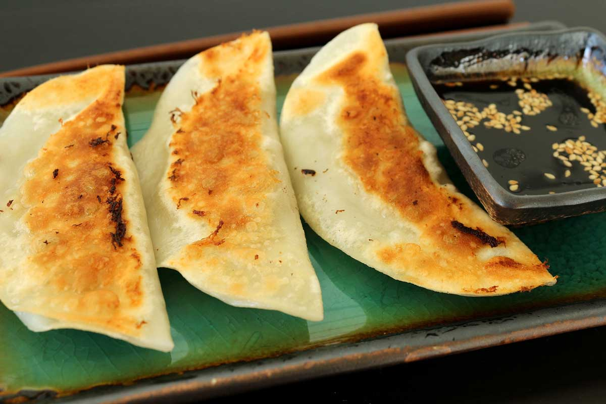 Three half moon shaped pan-fried dumplings on a green plate with dipping sauce.