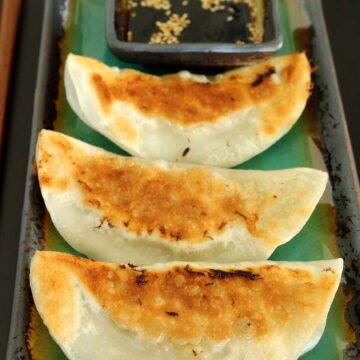 Closeup of pan-fried dumplings on a green rectangular plate.