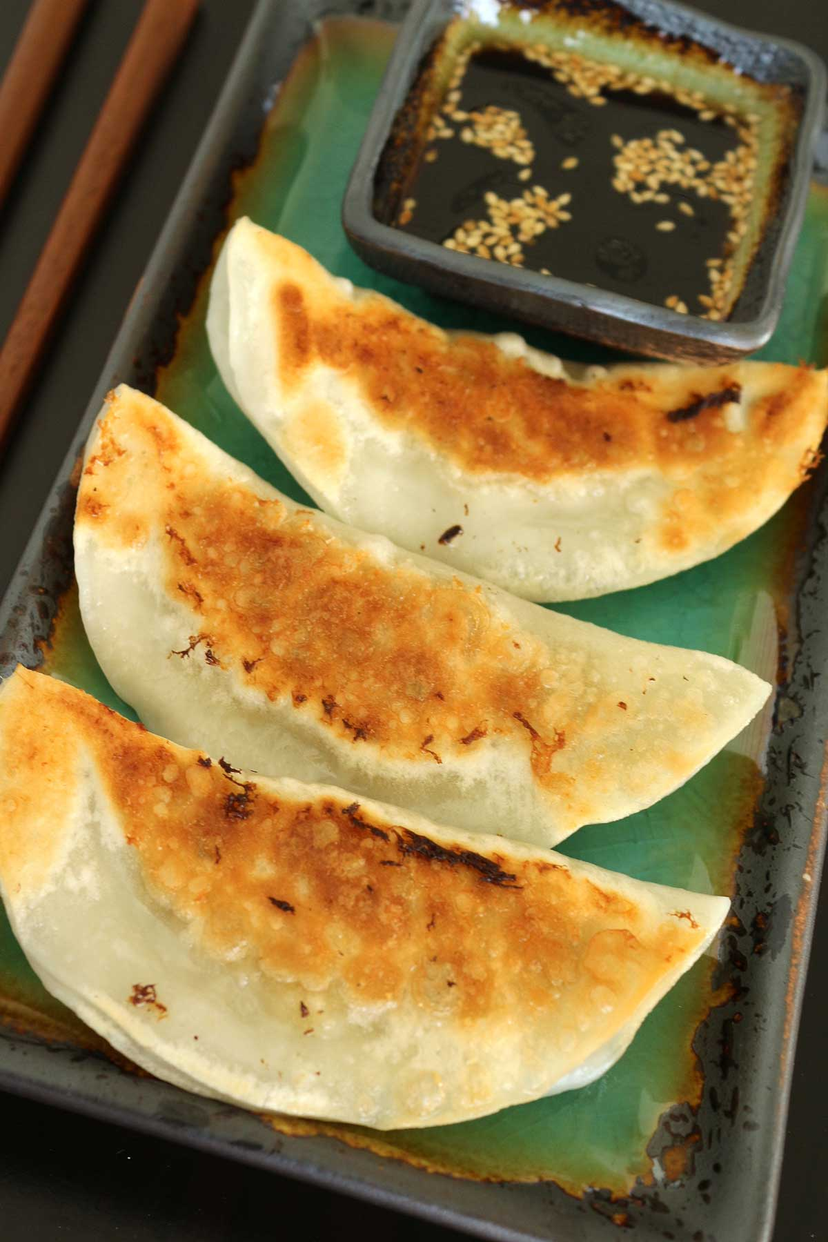 Closeup of 3 pan-fried dumplings on a plate with dipping sauce at the far end.
