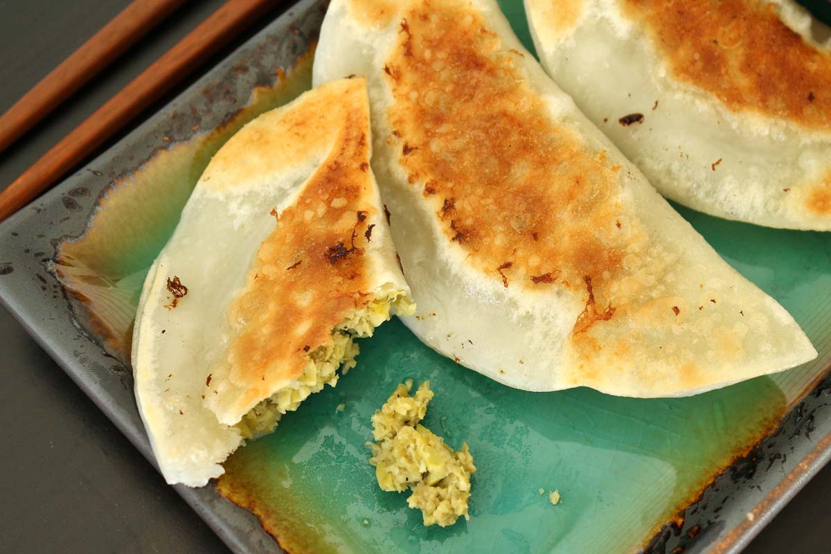 A bite taken out of an edamame dumpling, with 2 intact dumplings next to it.