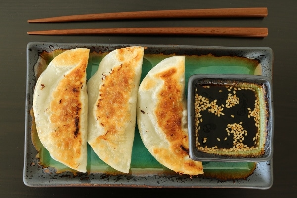 overhead view of pan-fried dumplings with dipping sauce on a green rectangular plate