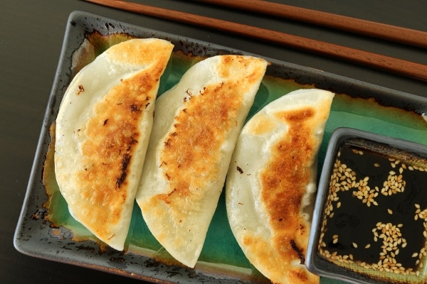 overhead view of 3 pan-fried dumplings on a plate with dipping sauce on the side