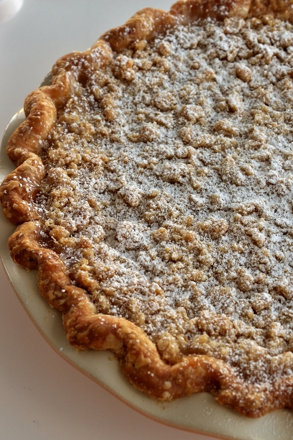 powdered sugar dusted over a pie with a crumb topping