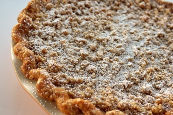 closeup of a pie with crumble topping dusted with powdered sugar