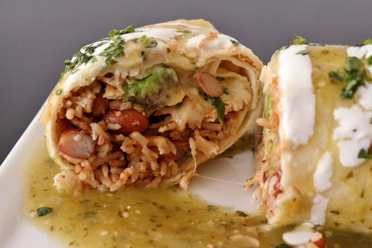 Closeup of a cross-section of a burrito showing off its rice, beans, and chicken filling.