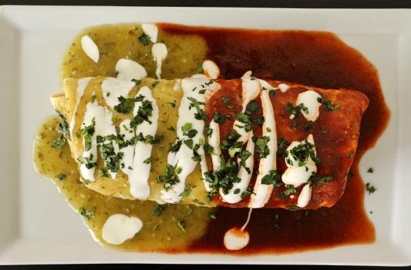 overhead view of a chicken burrito mojado on a white plate