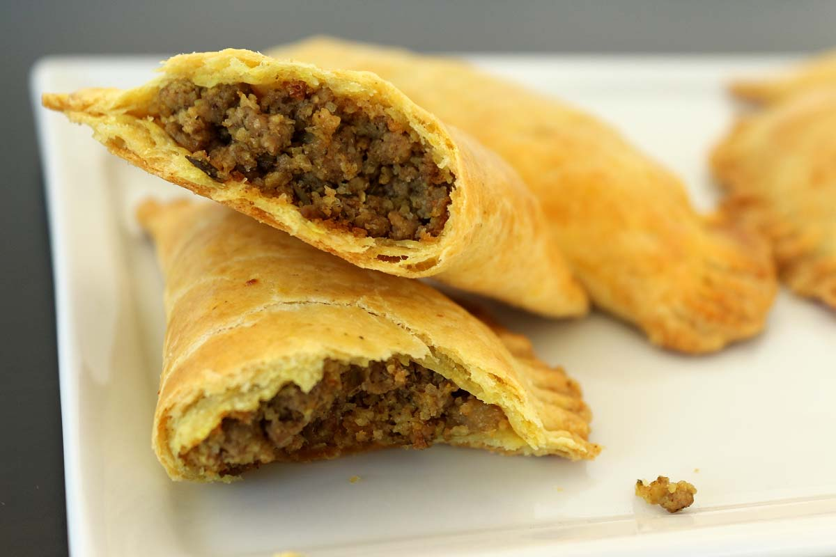 A Jamaican beef patty (a baked turnover) cut in half, showing the ground beef filling.