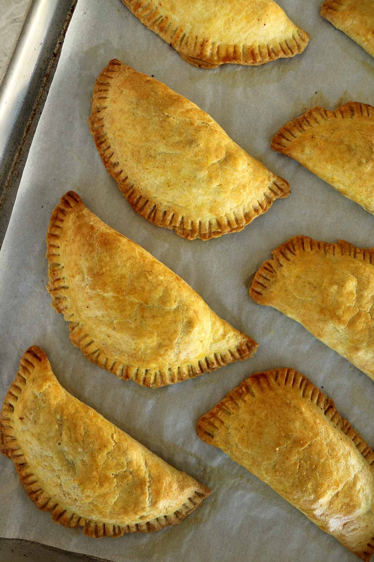 A baking sheet of Jamaican beef patties with golden crusts, and crimped edges.