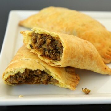 Closeup of a Jamaican beef patty cut in half, showing the ground beef filling.