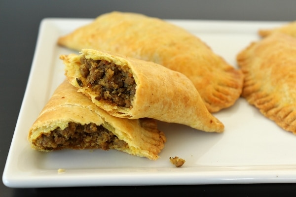 A Jamaican beef patty (a baked turnover) cut in half, showing the ground beef filling