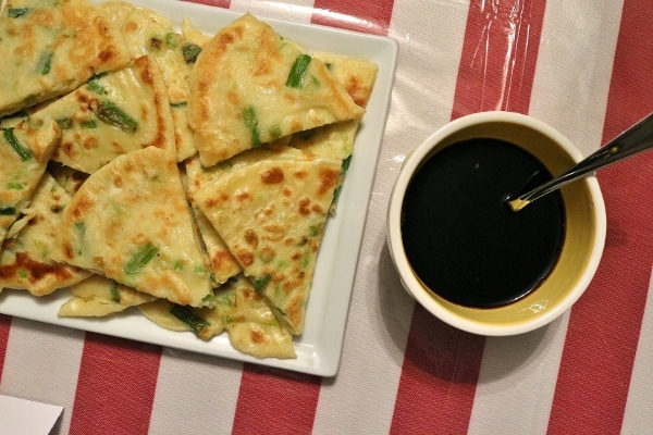 overhead view of a platter of Korean scallion pancakes and dipping sauce