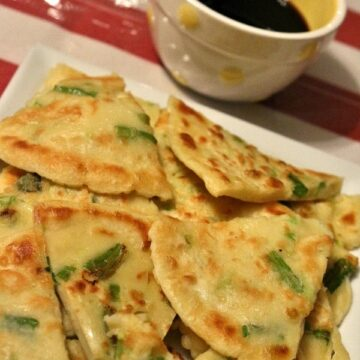 A close up of a plate of Korean scallion pancakes with dipping sauce