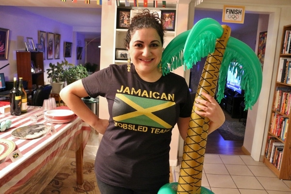 a woman holding an inflatable palm tree