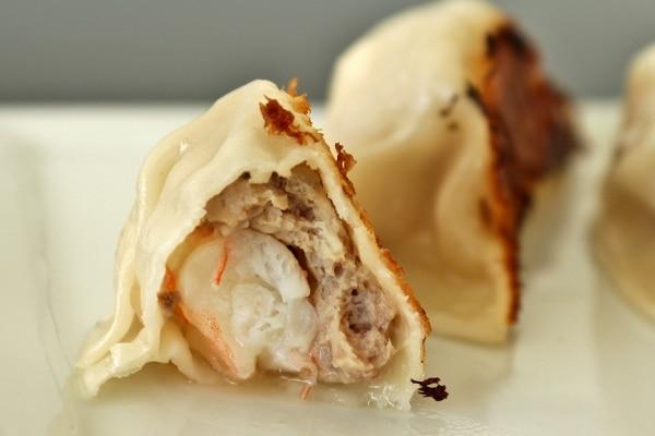 closeup of a pork and shrimp dumpling with a bite taken out