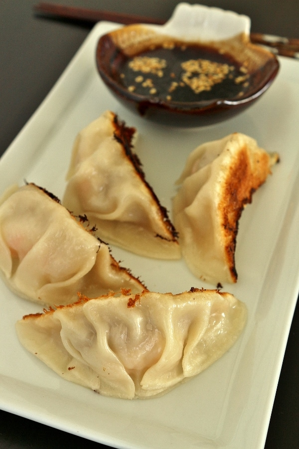 4 pan-fried dumplings on a rectangular plate with dipping sauce