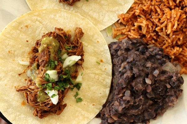Braised chicken taco with salsa verde, cilantro and chopped onion, served with refried black beans and Mexican rice