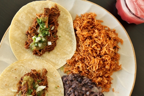 Braised chicken tacos with salsa verde, cilantro and chopped onion, served with refried black beans and Mexican rice