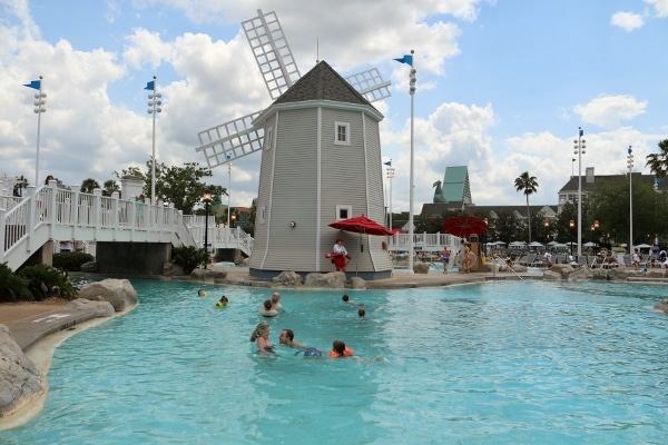 A group of people swimming in a pool in front of a windmill